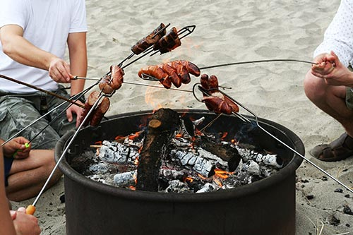 People barbecuing meat over a beach fire