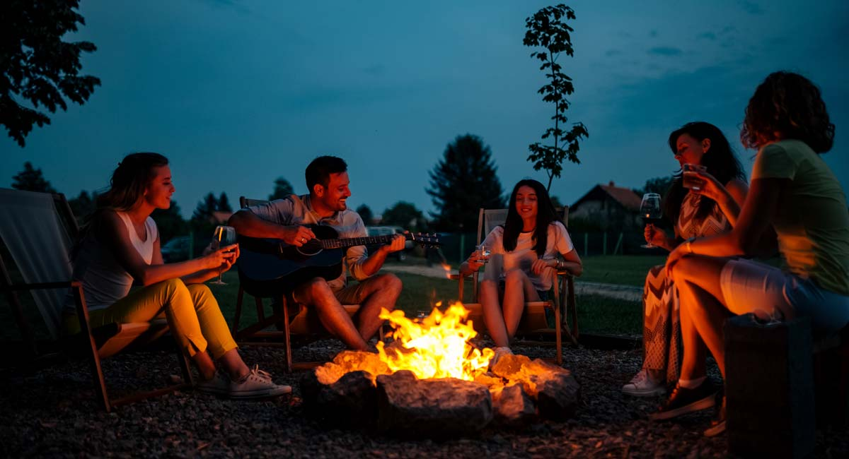 Firewood Link image with people sitting around a campfire